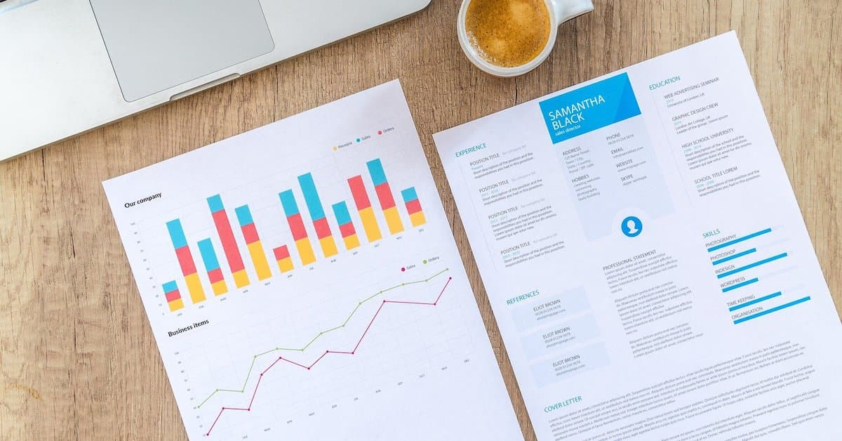 Printed paper on a desk showing a bar chart and a line graph alongside a CV