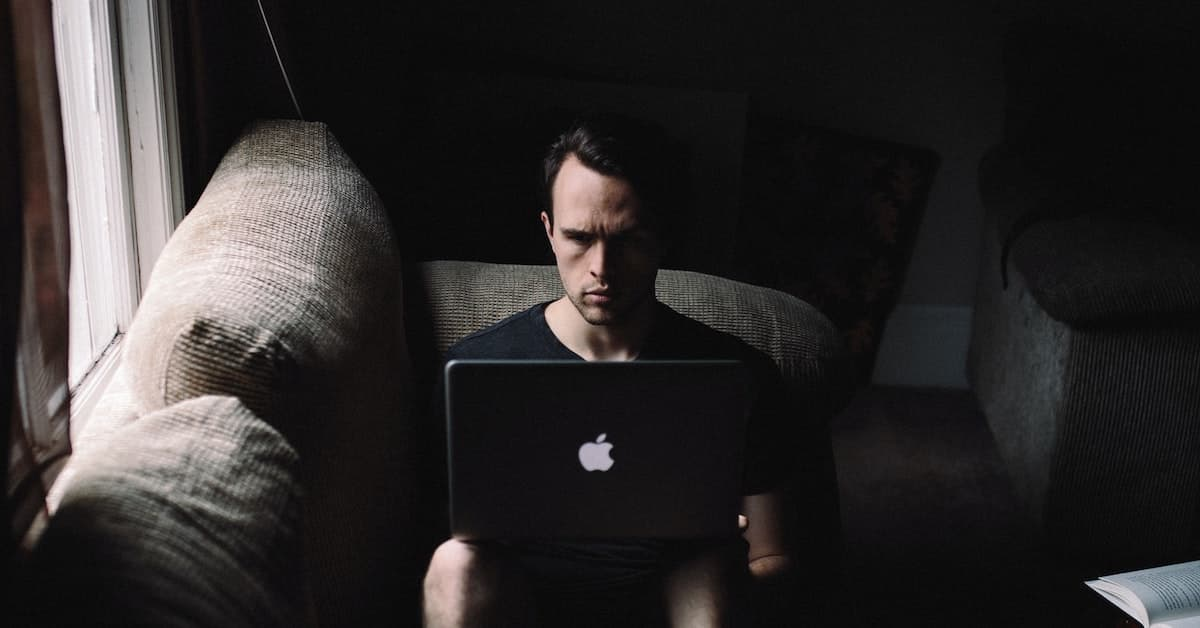 Image of a man sitting in a dark room using a macbook air