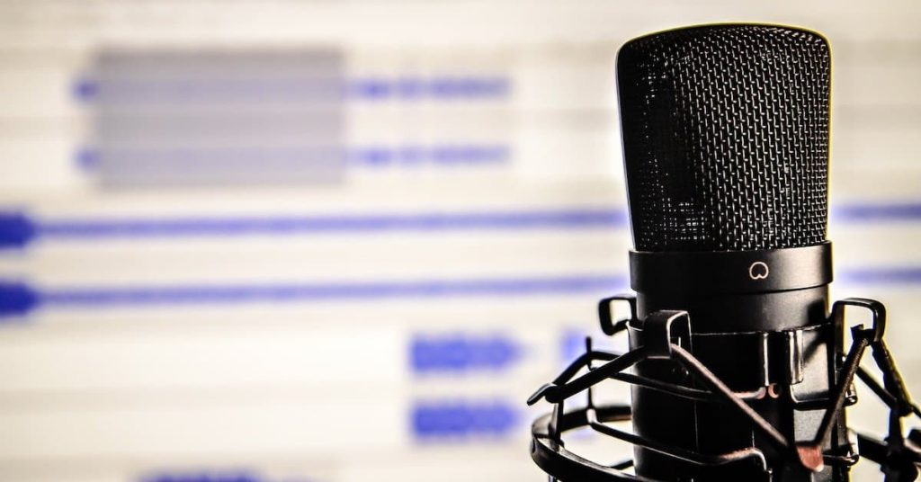 Image of a microphone in front of a computer showing audacity on screen
