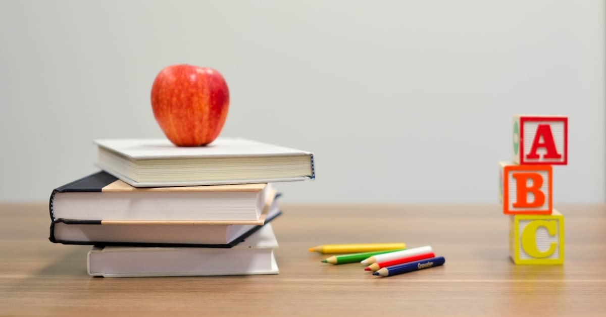 Image of an apple on top of stacked books on a desk and some building blocks stacked up with ABC