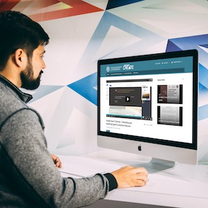 Image of a young man viewing a video on media Hopper create via an iMac