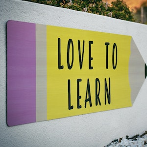 Image of a colourful sign in the shape of a pencil on a wall with the text 'Love to Learn' displayed.